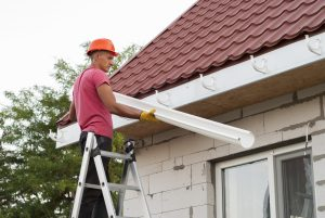 man with red shirt installing rain gutters for window az company